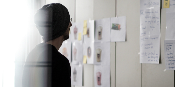 employee staring at a project board, symbolizing an individual's search for the right job and how important employee benefits for staff retention is