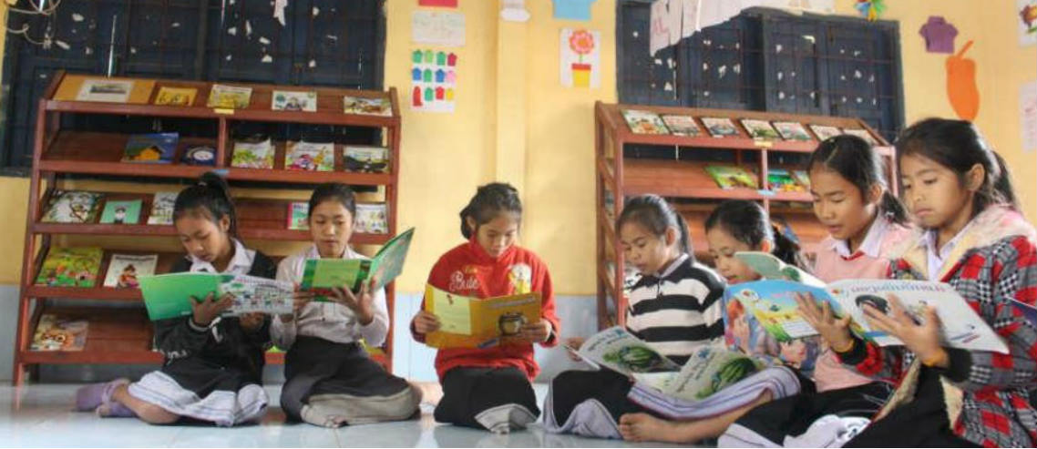 young girls from laos read books in a library built by a partnership between room to read and pacific prime