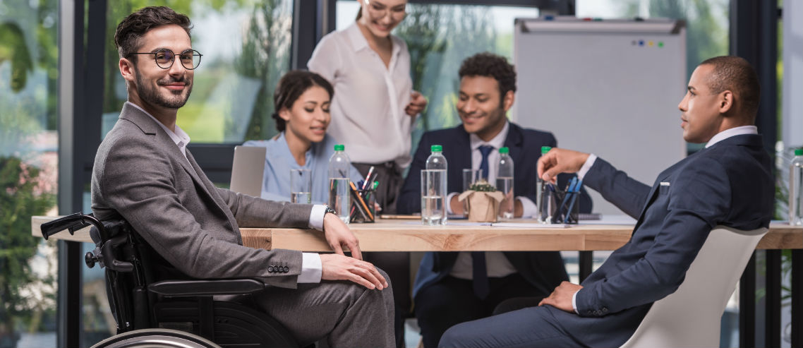a man in a wheelchair sits in the foreground whilst his professional work colleagues discuss something in the background, symbolizing the importance of understanding how diversity and inclusion can be supported by your group insurance and employee benefits