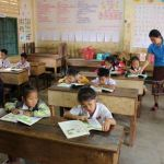 students read at their desks in a room to read and pacific prime built school in laos
