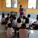 a teacher reads to a classroom of young students in a room to read and pacific prime built school in laos