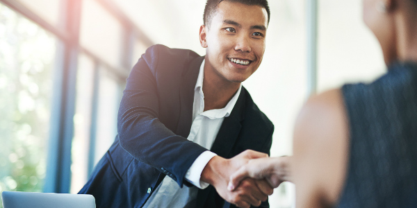 an insurance broker shakes the hand of a client after providing HR support for employee benefits