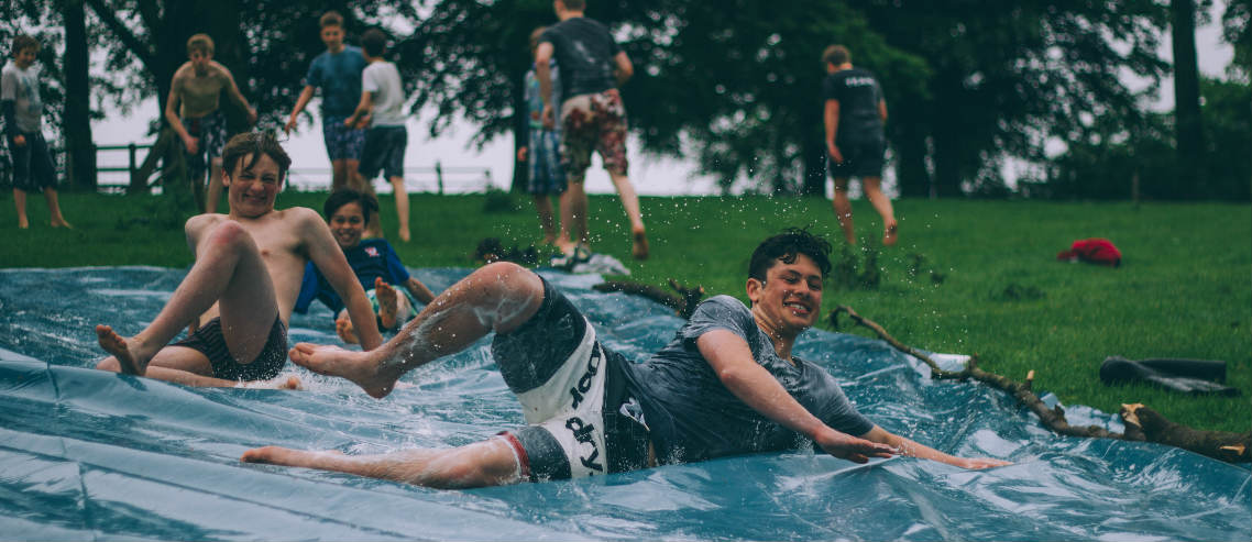 boys play on a slip and slide at the park promoting the benefits of free play