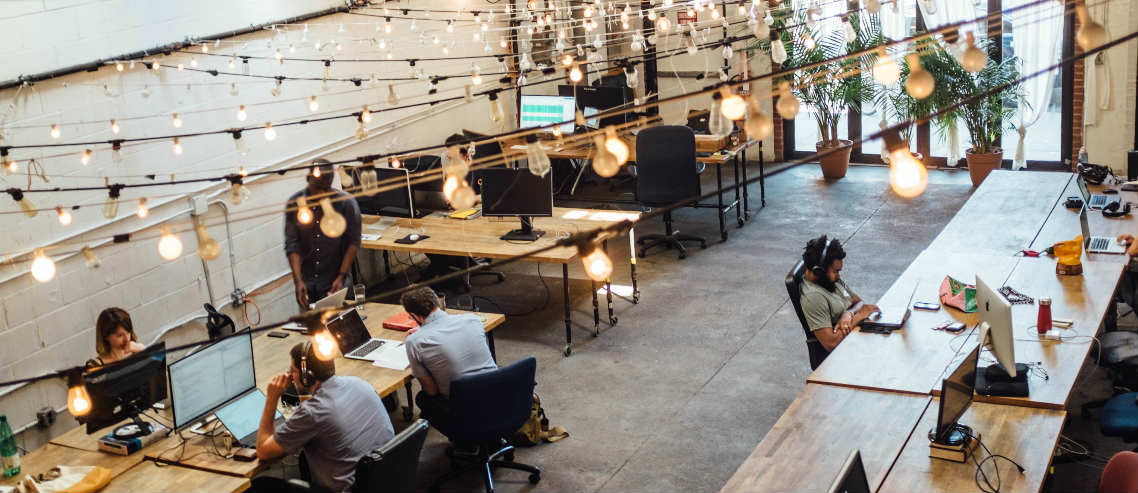 a group of employees work collaboratively in an diverse and modern workspace, outlining the importance of understanding what types of employee health benefits might be useful in today's working environment