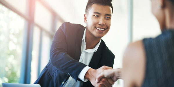 Asian man shaking hands after discussing a continuation plan