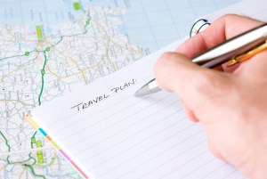 Hand writing travel plan in a lined spiral notepad arranged on a map