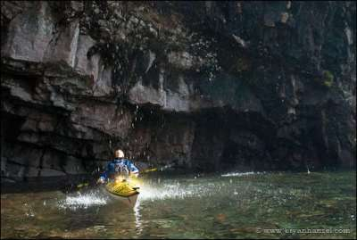 Lake Superior kayaker under a waterfall.