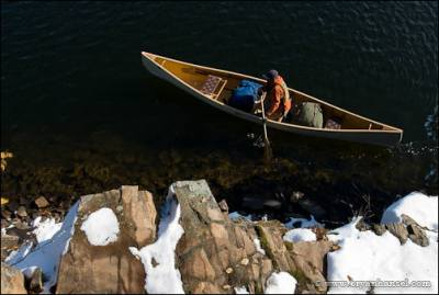 Canoeing past a snowy cliff on Mink Lake.