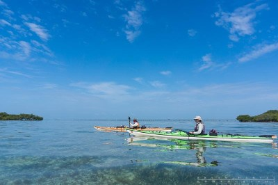 Amy and Dave Freeman of the Wilderness Classroom paddle past Seven Mile Bridge in the Florida Keys.