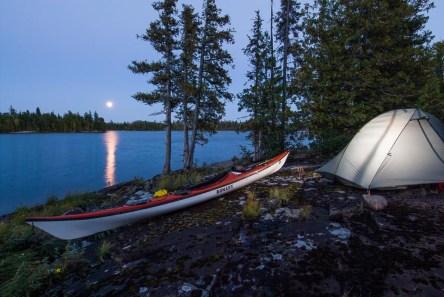 A kayak sits in front of a tent at moonrise. Lake Nipigon, Ontario.