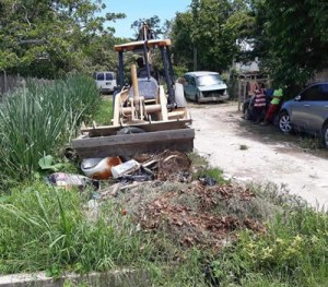 Heavy equipment is used to clear debris and excavate.