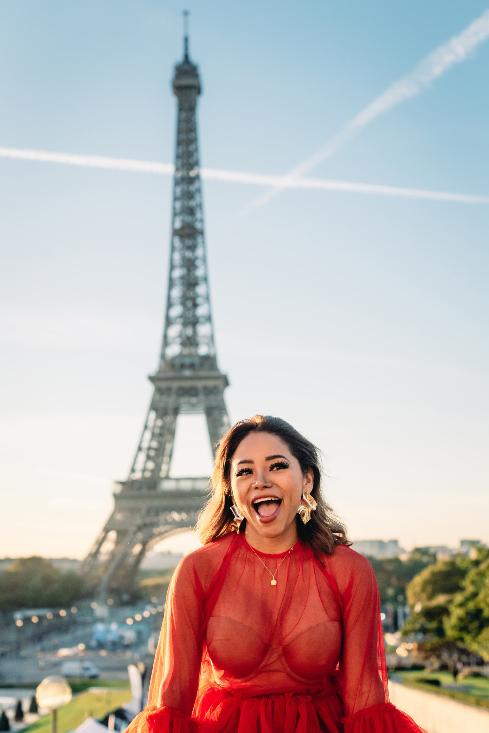 Portrait photography session in front of the Eiffel Tower in Paris, featuring a young woman in a mesh red dress and big gold earrings at sunrise