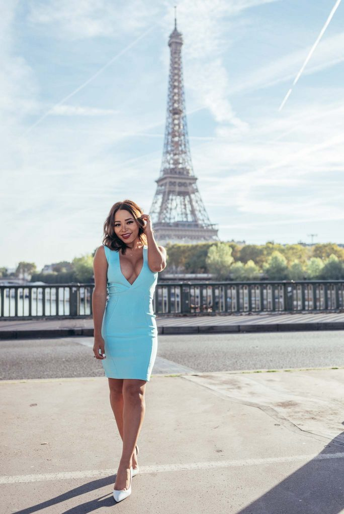 portrait of woman in front of the eiffel tower in paris with a wider angle 35mm focal length and with full tower visible in the background