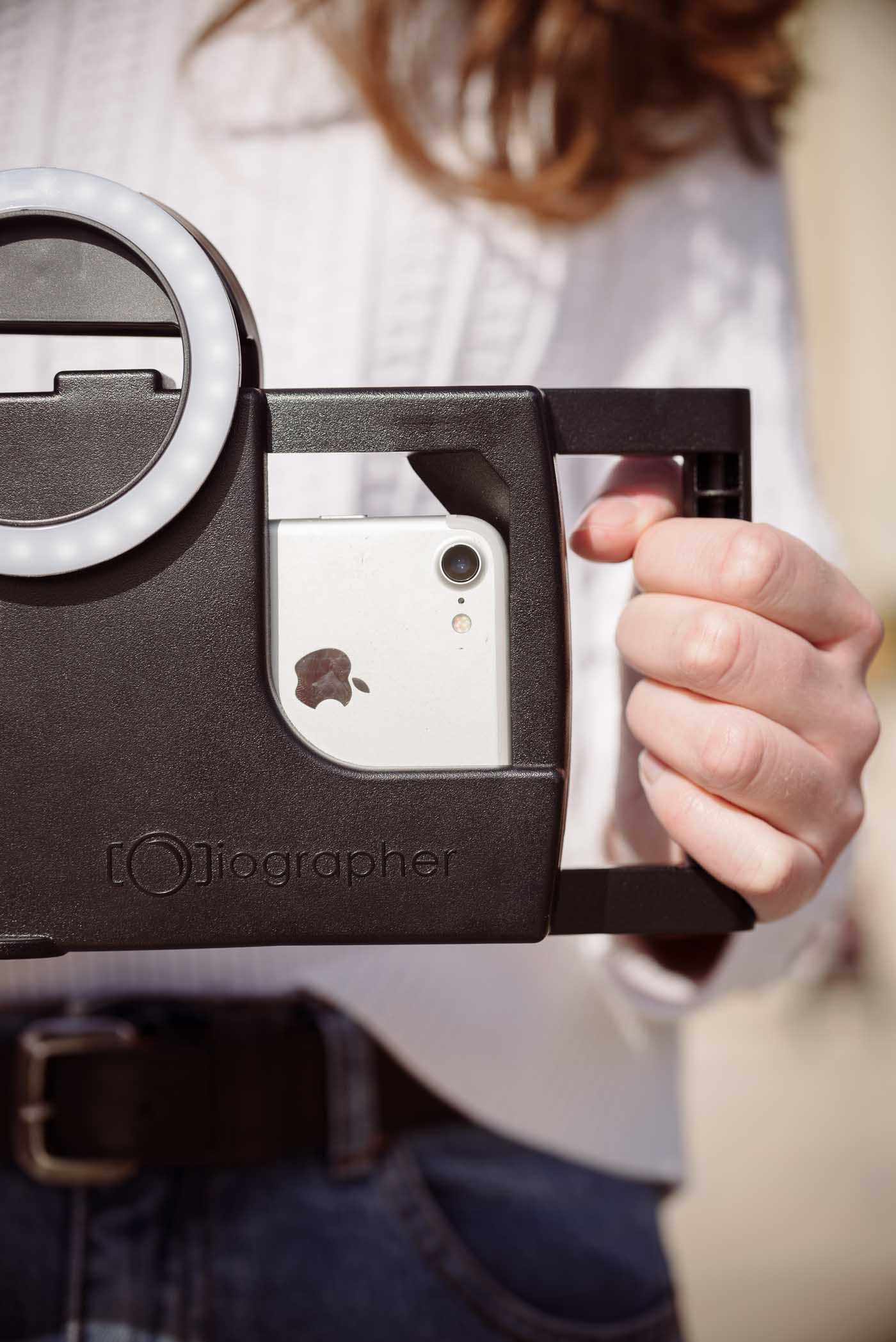 close up photo with model holding iOgrapher filming case with iPhone and ring light