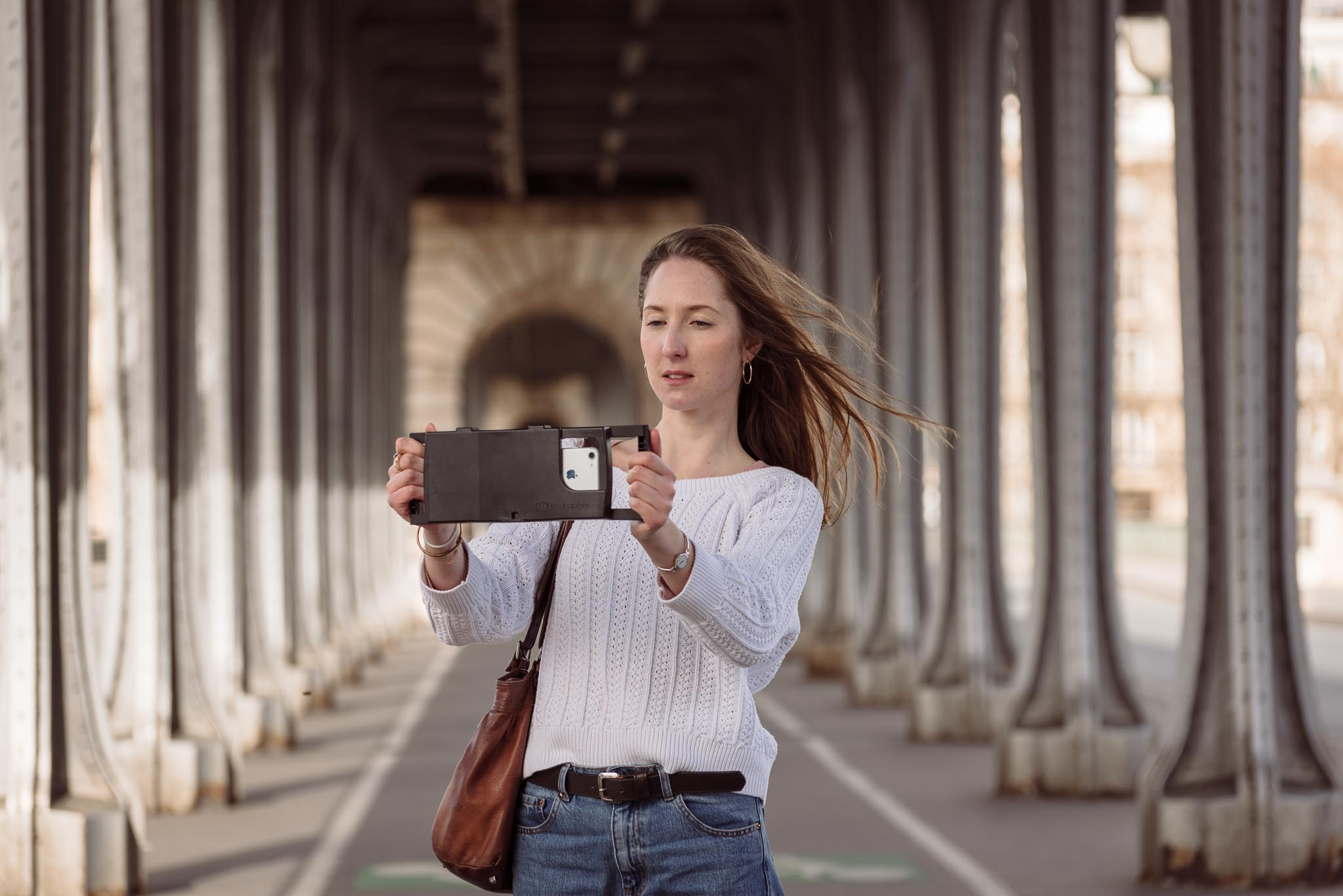 lifestyle photography for tech product in Paris on the Bir-Hakeim bridge