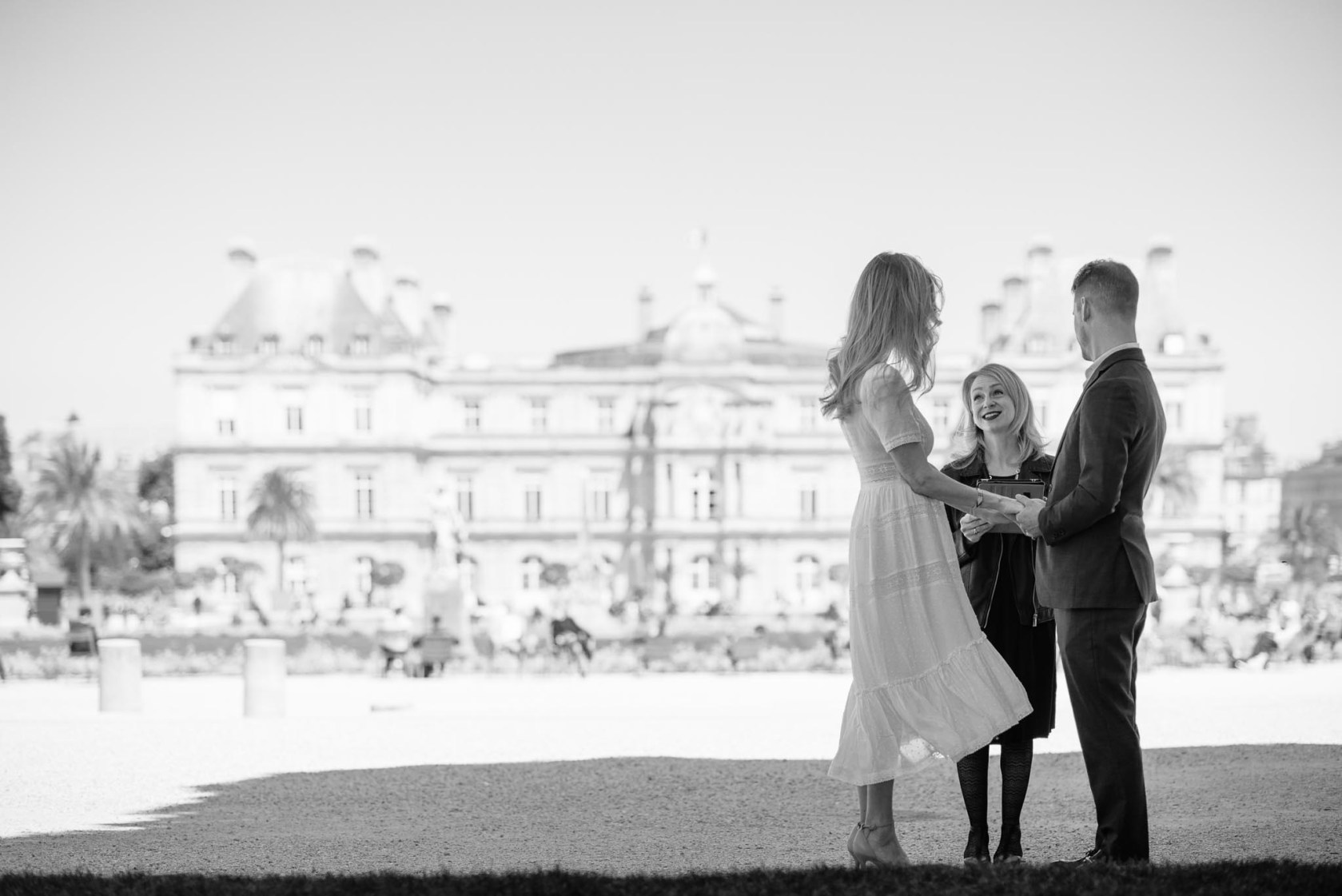 Black and white photo of a couple at an elopement ceremony in the Luxembourg Gardens in Paris, officiated by Michelle Wahila of Ruffled by Grace
