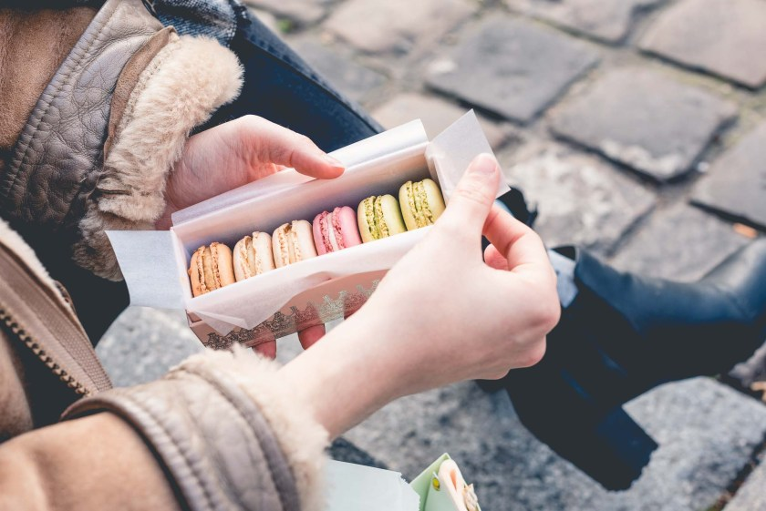 Paige Gribb Photography in Paris, France: lifestyle photo of woman's hands holding box of Ladurée macarons