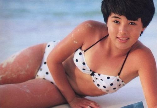 砂を足につけて砂浜に寝転ぶ水玉模様の水着が似合っている井森美幸