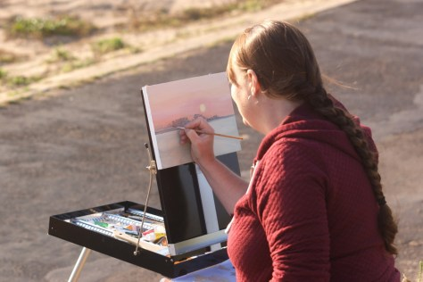 Lara Cobden painting the sunrise at POW15, photo by Katy Jon Went
