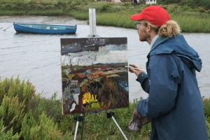 Artist Jack Godfrey painting Brancaster Staithe at POW16. Photo by Katy Jon Went