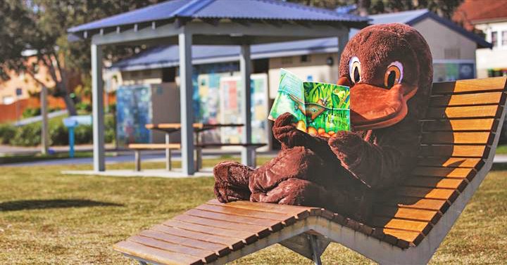 Platypus mascot in deck chair reading