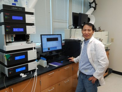 Dr. Liu next to his lab equipment