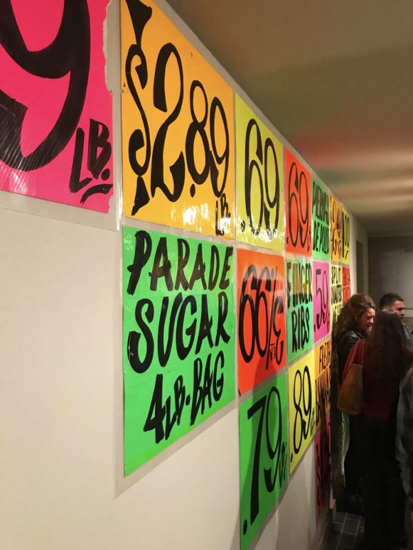 Colorful mercado signs line the wall.