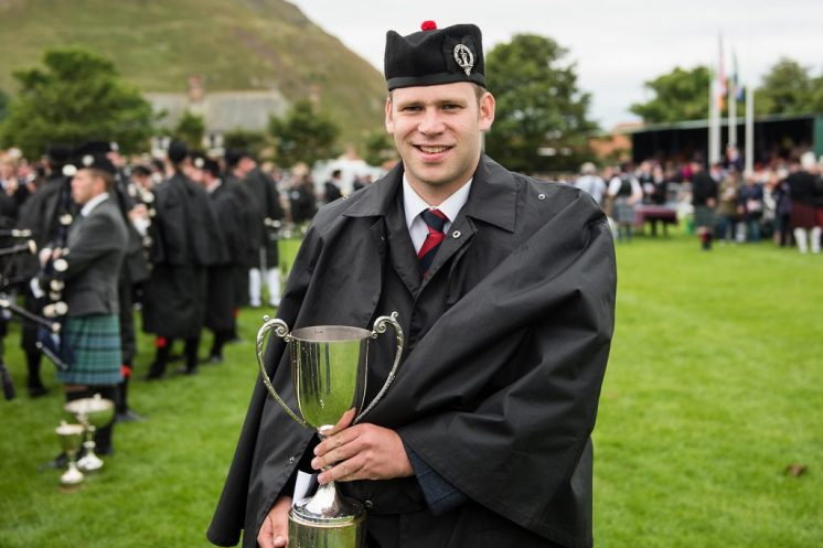 Pipe Major Keith Bowes Jr picking up the Grade 1 fourth place trophy