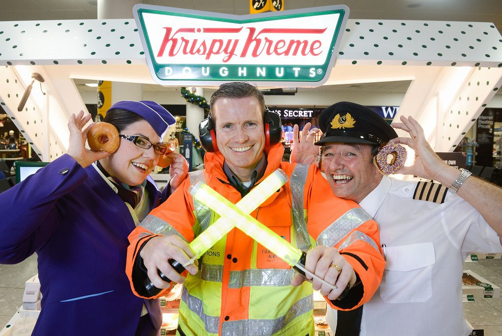 Picture by Nick Ponty  19/11/16 Krispy Kreme opens at Glasgow Airport  Logan Air Cabin Crew manager Avril McEwan and Pilot Eddie Watt try out some doughnuts with Glasgow Airport airside operations officer Derek Paterson (centre).