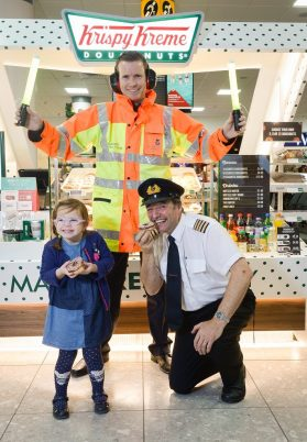 Picture by Nick Ponty 19/11/16 Krispy Kreme opens at Glasgow Airport Logan Air Pilot Eddie Watt try out some doughnuts with Glasgow Airport airside operations officer Derek Paterson (centre) and passenger Molly Sinclair (4) .