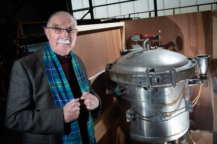 Clarke Wallace, wearing fair trade tartan, with the historic dye vat