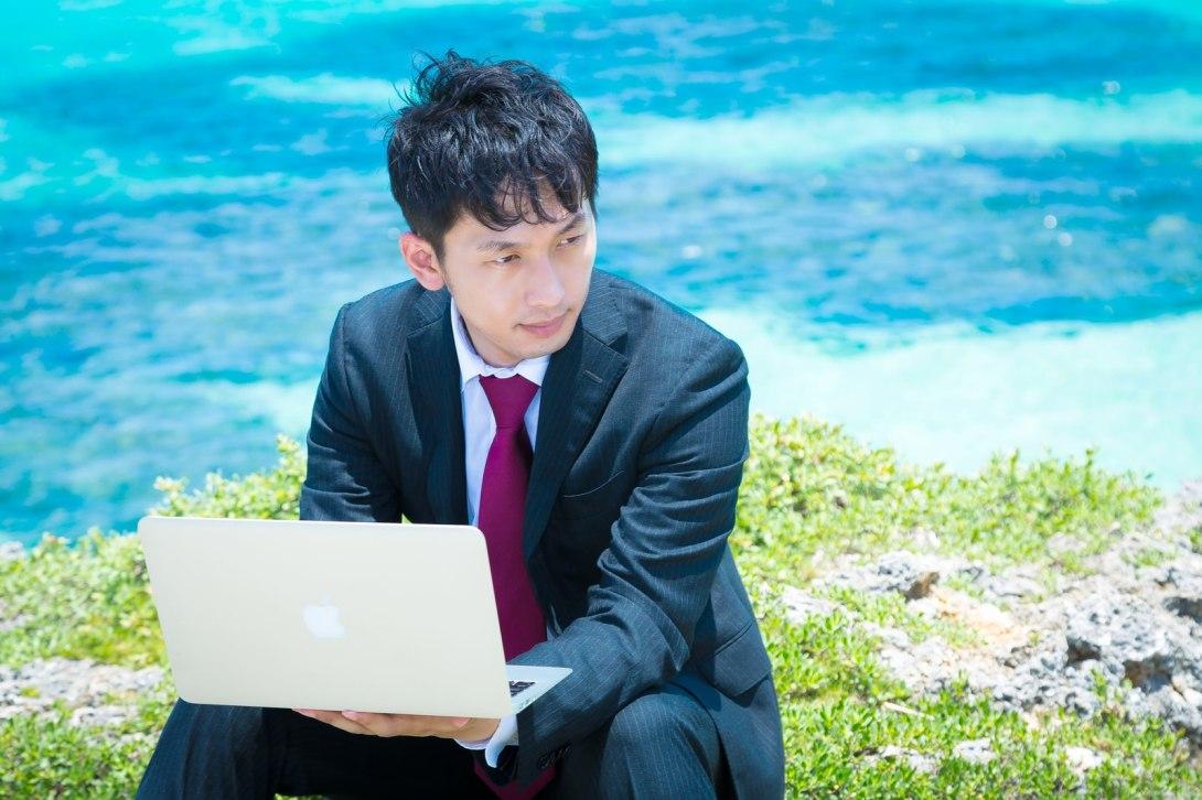 「青い海をバックにMBAで作業を行うビジネスマン」[モデル:大川竜弥]