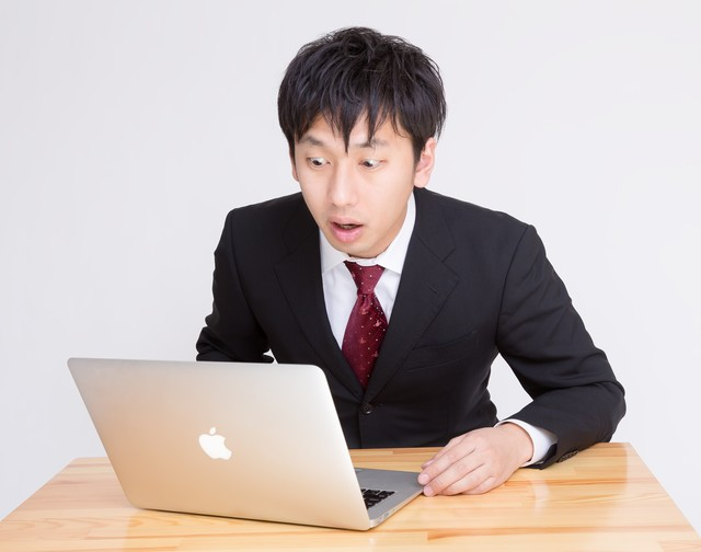 PCを見て「ヤバいことになった」っと驚く表情のビジネスマン