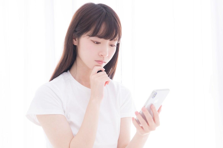 「スマホを眺めて考え込む白いTシャツの女性」の写真[モデル:川子芹菜]