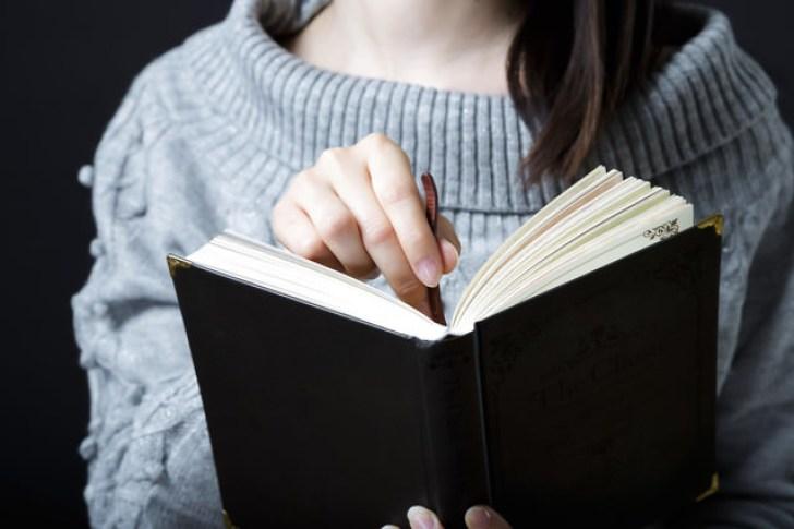 本に栞をはさむ女性