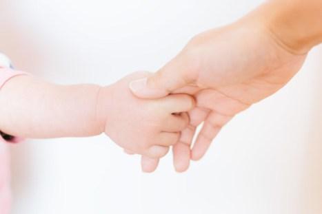 親の手を握る赤ちゃんの手