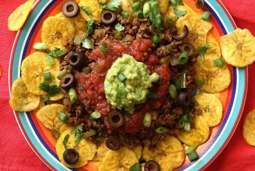 hearty plate of nachos with a spicy meat and veggie dip