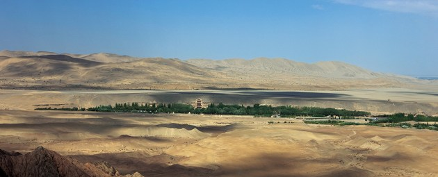 The cave temples of Mogao, carved into the cliff face along the Daquan River, are shaded by poplar trees planted in the 20th century and surrounded by austere desert. The nine- story temple can be seen at the center. Beyond the plateau above the cliff rise the Mingsha Shan—the Dunes of the Singing Sands. Photo: Sun Zhijun, ©Dunhuang Academy