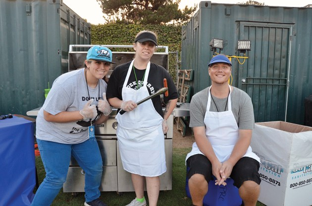 Recreation Center employees Kaila Osorio (left), Ashley Johnson and Jeff Owens serve free hot dogs.