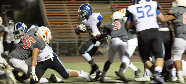 Running back Innnocent Okoh dodges through a hole with help from offensive guard Jonathon Molina. Photo: Drew Vaupen