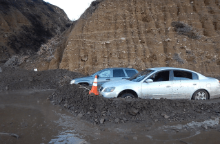 Two cars stuck in a mudslide along the PCH. Photo: Caltrans (Twitter).