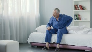 man suffering from back pain in bed