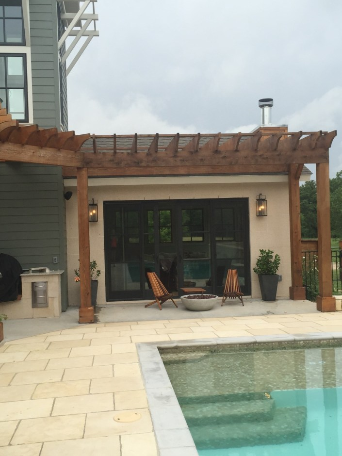Modern pool with wooden furniture and fire pit