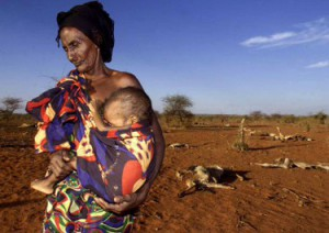 YEAREND PICTURES 2000 - Ruqia Aroo, 80, carries her malnourished grandson Khalif Sheikh Adan, 5, near the carcasses of her dead herd of cattle near Afder, 1100 kms south east of Addis Ababa, April 18, 2000. (CANADA OUT) gm/Photo by George Mulala REUTERS