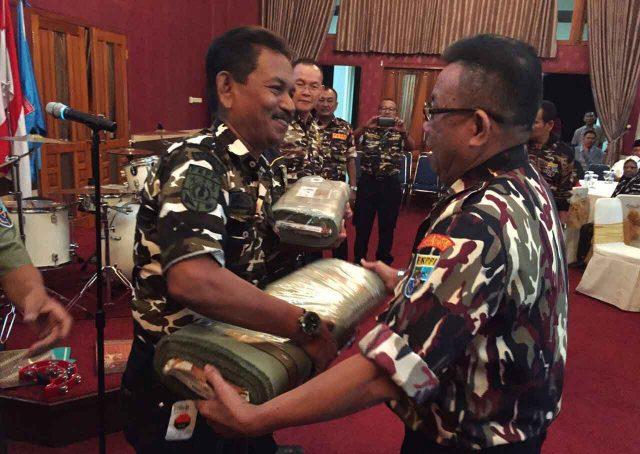 Ketua DPD FKPPI Sumsel memberikan bahan pakaian seragam FKPPI kepada pengurus daerah.