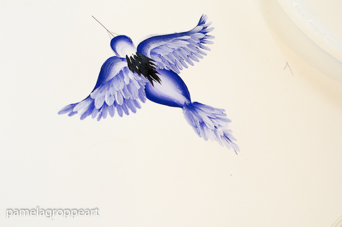 Add black feathers to shoulders and back of flying blue bird