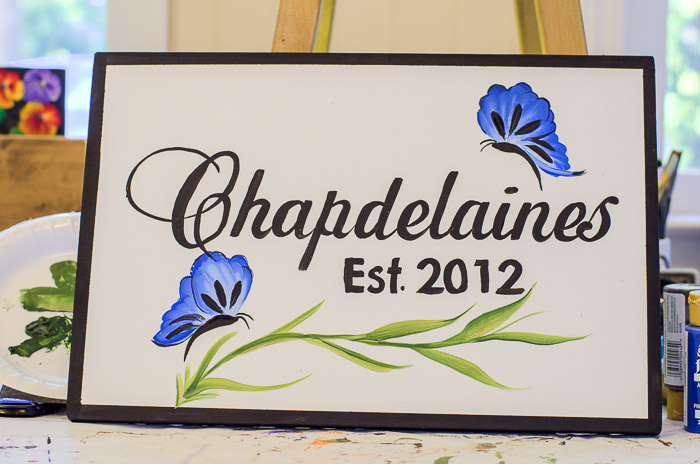 Blue butterflies painted on a sign