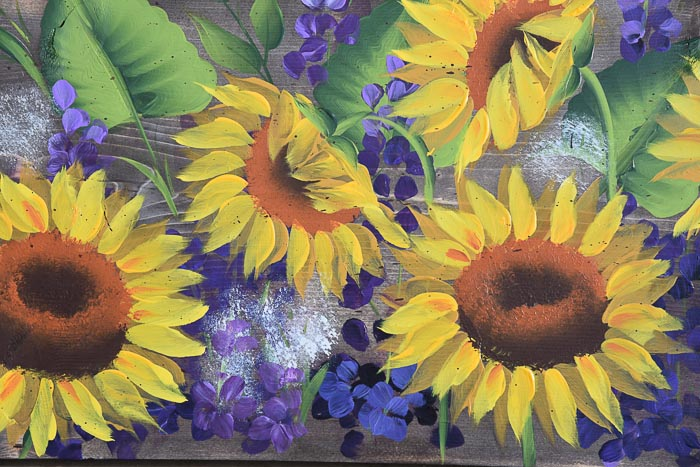 close up of sunflower and delphiniums painting on stained wood
