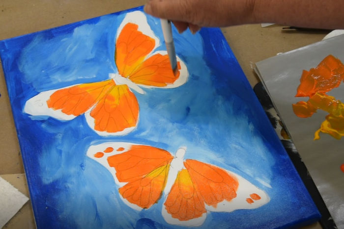 Add more orange to the paint brush then apply to butterflies wings