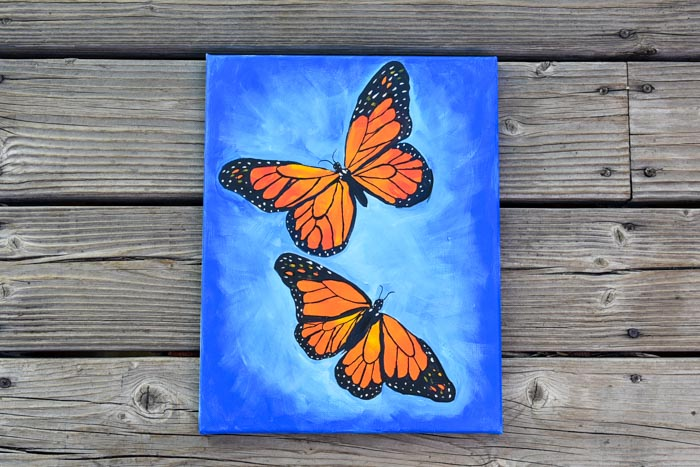 Monarch Butterfly painting, blue background with 2 butterflies